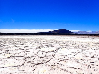 Vue sur le sombre volcan Carachi Pampa de l'autre côté du salar qui l'entoure
