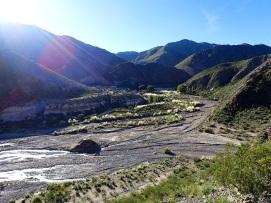 Vue sur le village Las Papas de l'autre côté de la rivière dont la route emprunte l'itinéraire pour s'enfoncer dans les montagnes