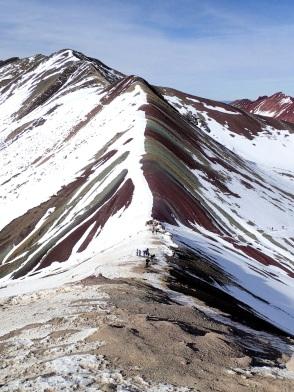 Vue sur la montagne de l'Arc-en-Ciel, dont les couleurs vives contrastent avec la couche de neige qui persiste sur le versant Sud